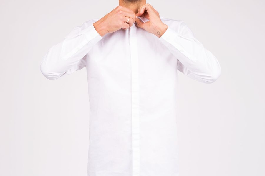 Homme qui boutonne chemise blanche