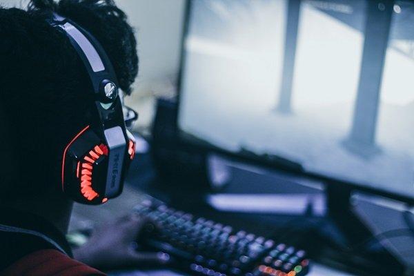 Person mit Headset spielt Videospiele an einem Gaming PC, den es während der Cyber Monday Angebote oft reduziert gibt