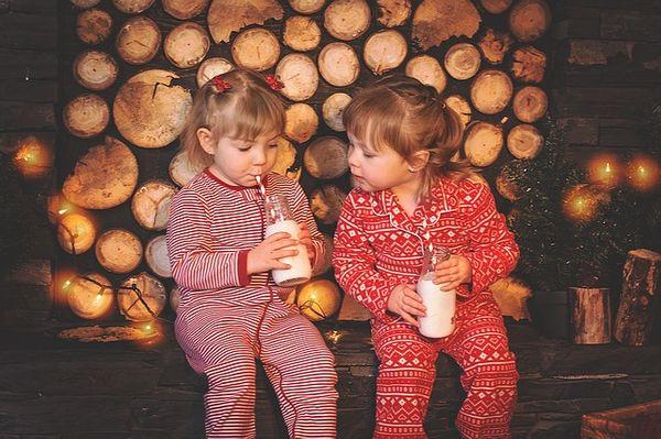 Enfants en pyjama devant des décoration de Noël