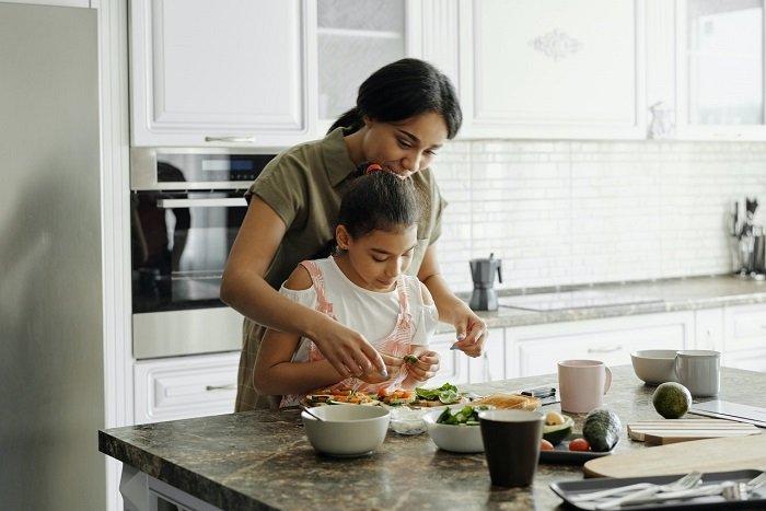 Mutter und Tochter kochen und backen gemeinsam in der Küche