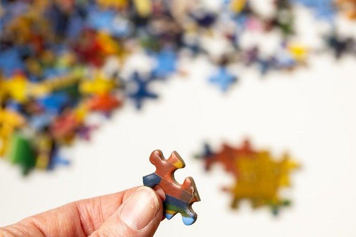 Person hält ein Puzzlestück in der Hand während weitere Teile im HIntergrund liegen