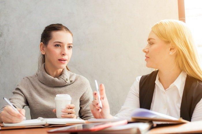 Zwei Frauen mit Notizen lernen gemeinsam eine Fremdsprache als Hobby