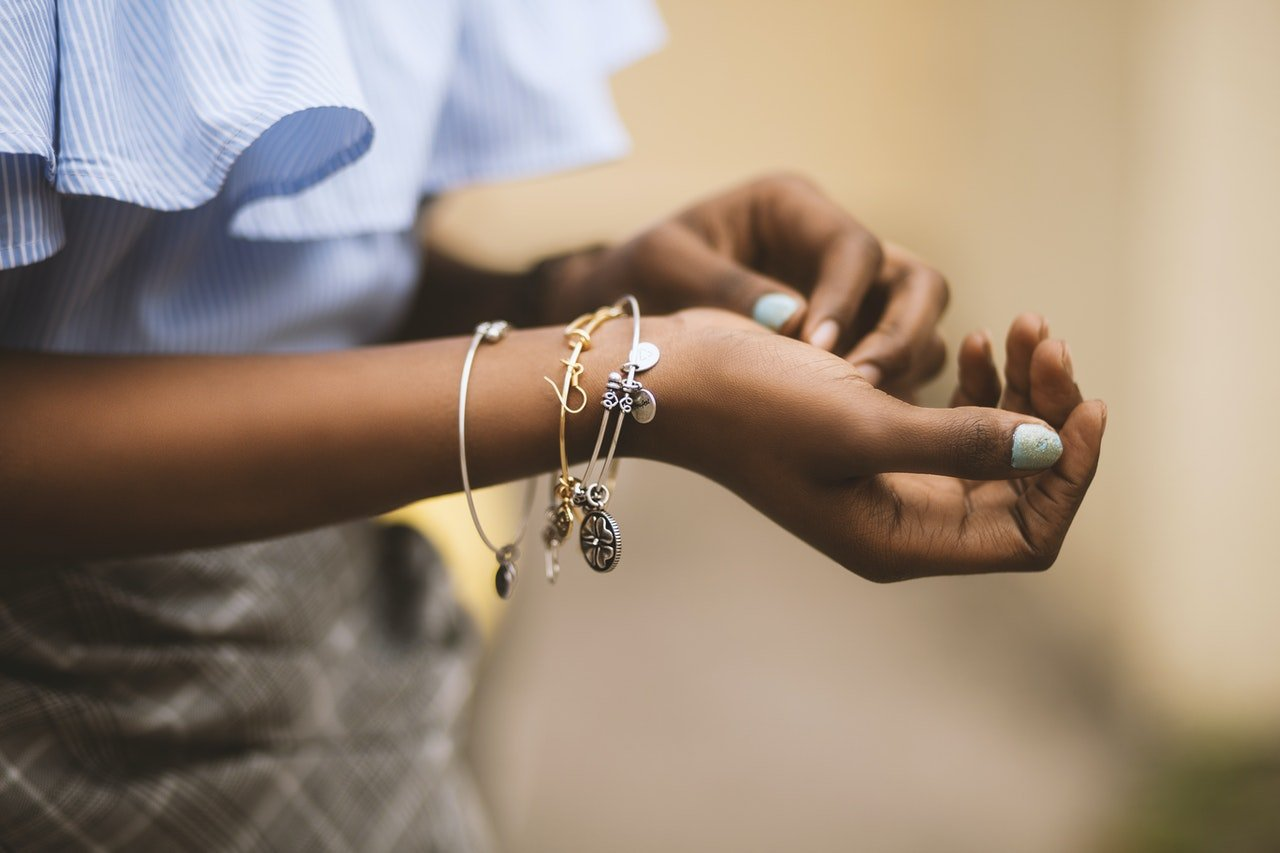 Femme en chemisier bleu qui ajuste ses bijoux