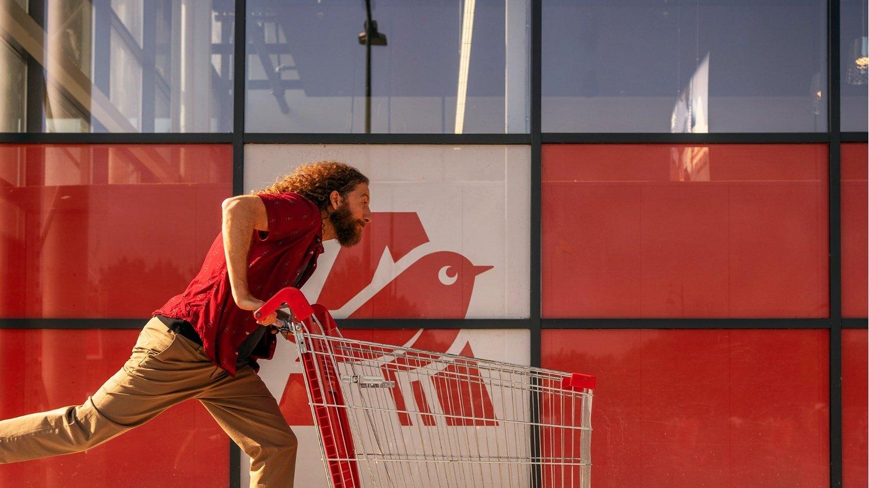 Homme poussant un caddie pour le Black Friday Auchan