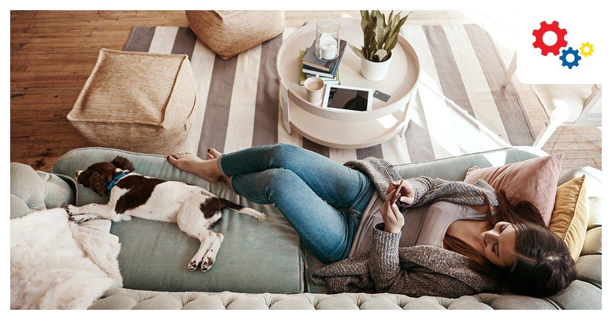 Femme allongée sur un canapé gris tenant un smartphone