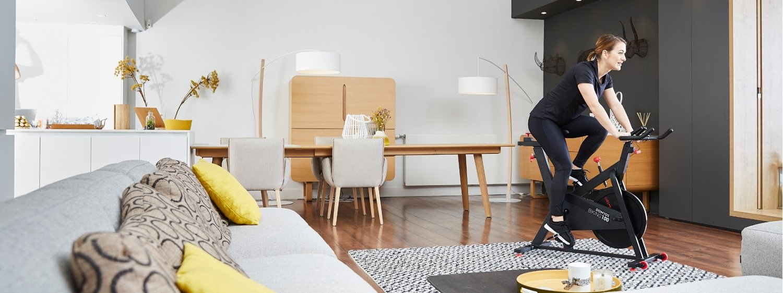 Femme en train de faire du vélo d'appartement dans un salon moderne