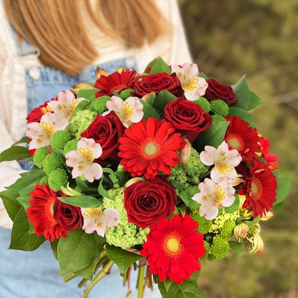 Femme en salopette bleue tenant un bouquet de fleurs rouges et roses Florajet