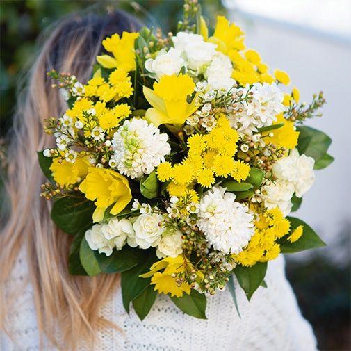Une femme en pull blanc porte un bouquet de fleurs jaunes