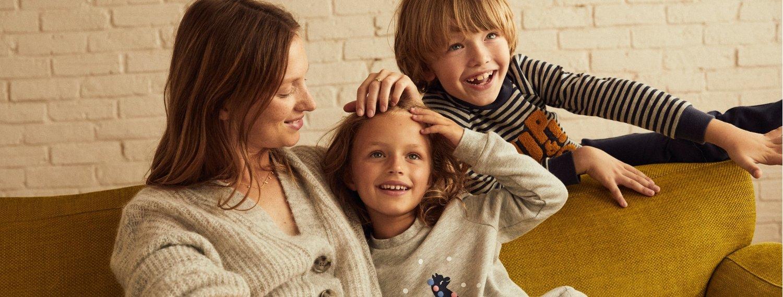 Maman et ses deux enfants sur un canapé jaune moutarde La Redoute