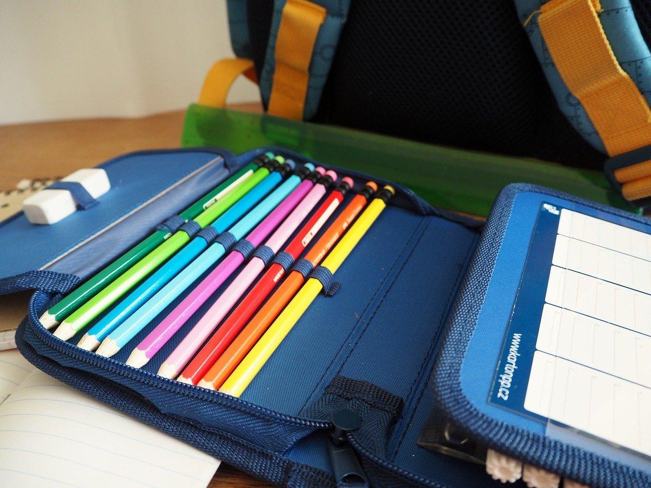 Pochette bleu marine de crayons de couleurs posée devant un cartable