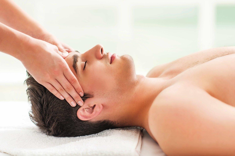 Homme allongé recevant un massage du visage