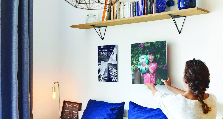 Femme brune qui accroche un tableau MonAlbumPhoto au dessus d'un canapé bleu