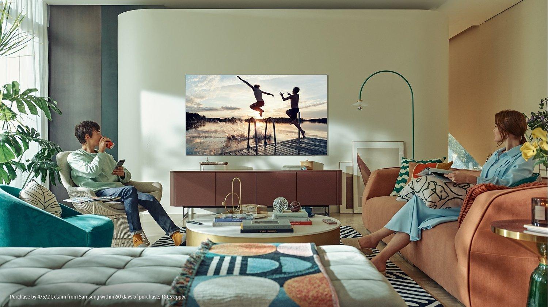 Couple dans un salon design qui regarde la télé sur un écran plat Samsung