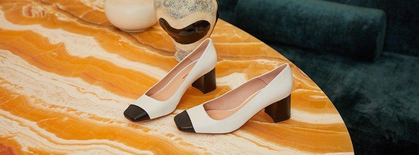 Paire des chaussures à talons blanches à bouts carrés noirs sur une table orange