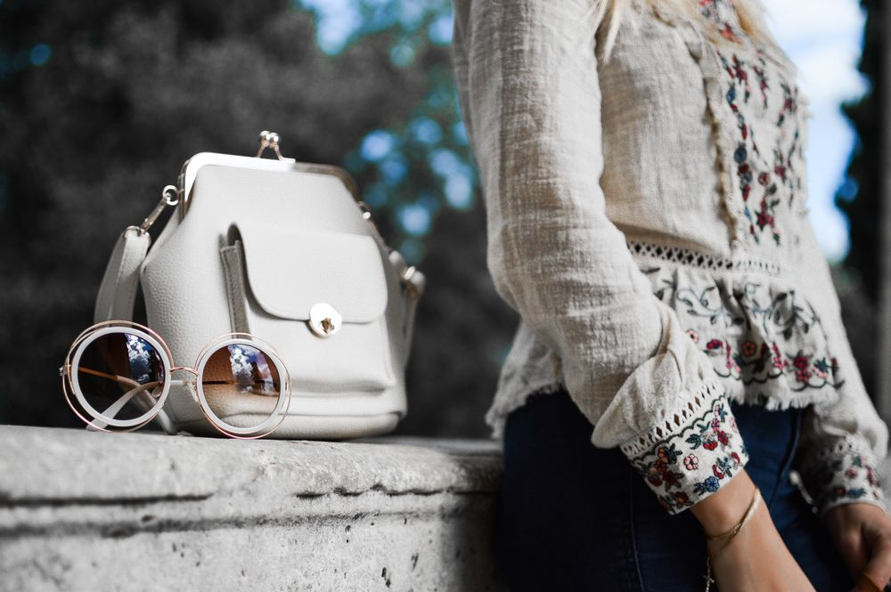 Femme adossée à un muret avec lunettes de soleil et sac à main de luxe