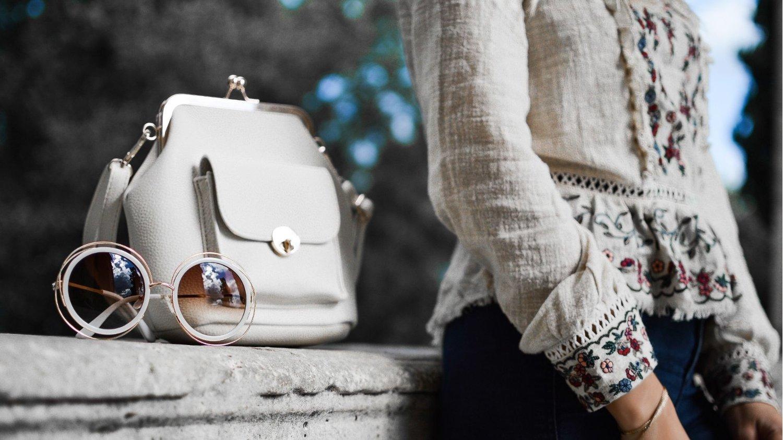 Frau in Designerkleidung mit edler Handtasche und Sonnenbrille, die es in Black Friday Angeboten für Markenkleidung günstiger geben wird