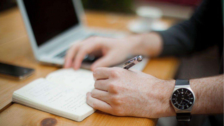 Mann erstellt auf einem Notizblock eine Liste während er auf dem Laptop nach Black Friday Angeboten sucht