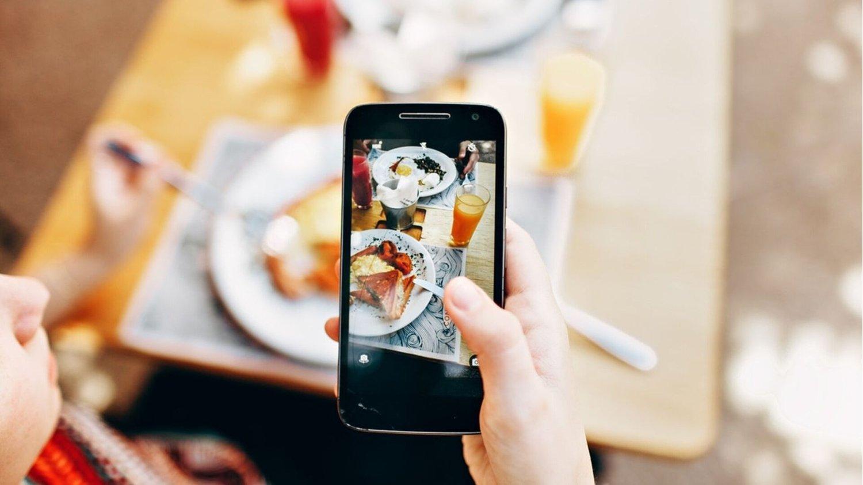Person fotografiert Essen mit Smartphone