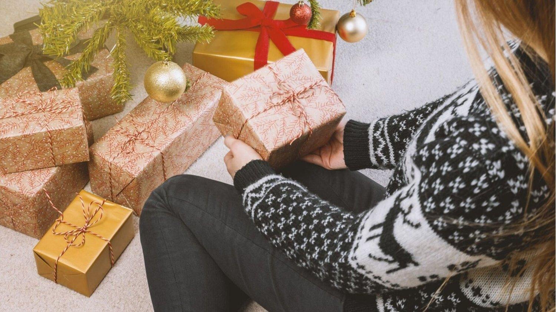 Junge Frau in Pullover kniet neben Weihnachtsgeschenken unter dem Christbaum